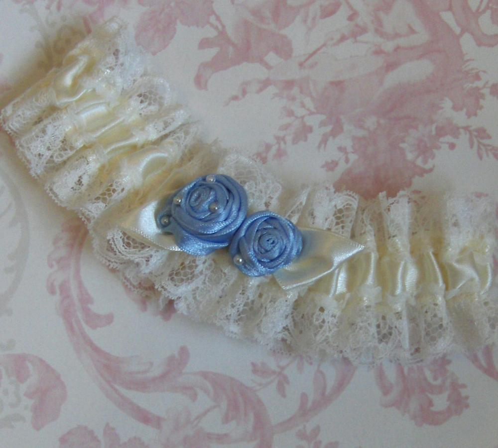 Ivory bridal garter with blue roses.